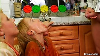 Pissing milf and daughter get fucked together in the kitchen