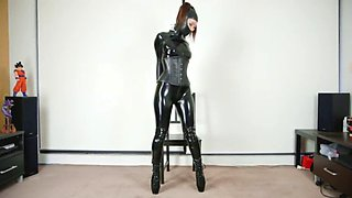 girl in catsuit bound with armbinder and hooded
