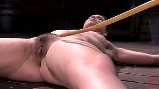 swollen nipples clutched between two wooden sticks