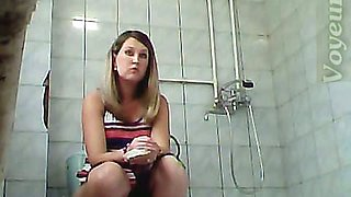 Blonde amateur lady in sexy dress pisses in the toilet room
