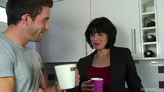Mature gal seduces a guy while wearing black stockings in the kitchen