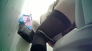 Brunette sweetheart in black stockings pisses in the toilet room