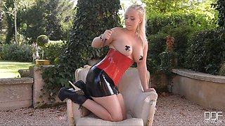 Cranky Mistress wearing corset plays with her big assets in the garden